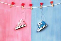 Espadrilles de bébé sur le fond rose et bleu, concept de fête de naissance Photographie stock