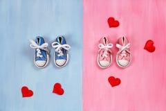 Espadrilles de bébé sur le fond rose et bleu, concept de fête de naissance Images libres de droits