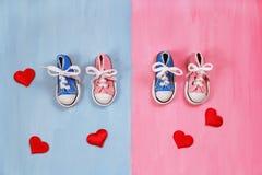 Espadrilles de bébé sur le fond rose et bleu, concept de fête de naissance Photos libres de droits