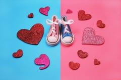 Espadrilles de bébé sur le fond rose et bleu, concept de fête de naissance Photographie stock libre de droits
