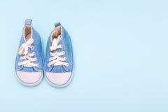 Espadrilles de bleus layette sur le fond bleu Photo stock