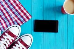 Espadrilles de Bourgogne, téléphone portable, café, chemise à carreaux sur lumineux Photo stock