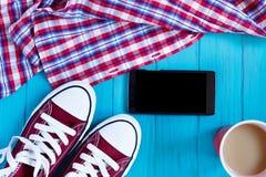 Espadrilles de Bourgogne, téléphone portable, café, chemise à carreaux sur lumineux Image libre de droits
