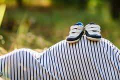 Espadrilles de butins sur le ventre d'une femme enceinte Image stock