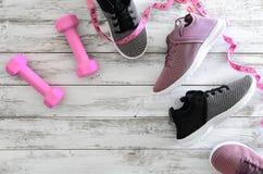 Espadrilles de chaussures du sport des femmes et haltères roses d'équipement, Photographie stock