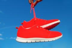 Espadrilles de chaussures de sports sur le fond de ciel bleu Photos libres de droits