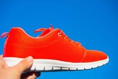 Espadrilles de chaussures de sports sur le fond de ciel bleu Images stock