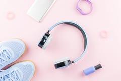 Espadrilles de femme, écouteurs, traqueur de forme physique et smartphone sur le fond de rose en pastel Concept de mode de sport  Images stock