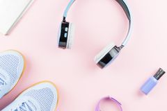 Espadrilles de femme, écouteurs, traqueur de forme physique et smartphone sur le fond de rose en pastel Concept de mode de sport  Photos stock