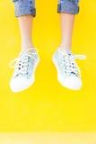 Espadrilles de jambes sur le fond jaune, mode de mode de vie Images libres de droits
