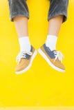Espadrilles de jambes sur le fond jaune, mode de mode de vie Image stock