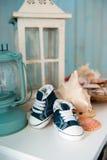 Espadrilles de jeans du ` s d'enfants dans l'intérieur de mer dans la perspective des coquillages Photo libre de droits