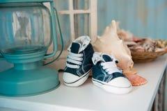 Espadrilles de jeans du ` s d'enfants dans l'intérieur de mer dans la perspective des coquillages Images stock