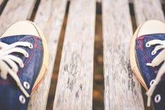 Espadrilles de jeans sur le vieil espace en bois de fond et de copie Image libre de droits