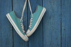 Espadrilles de la jeunesse de turquoise accrochant sur un clou Images libres de droits