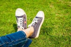 Espadrilles de la jeunesse sur des jambes de fille sur l'herbe Images libres de droits