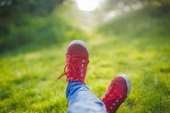 Espadrilles de la jeunesse sur des jambes de fille sur l'herbe Image stock