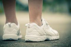 Espadrilles de la jeunesse sur des jambes de fille sur la route Photo libre de droits
