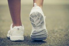 Espadrilles de la jeunesse sur des jambes de fille sur la route Photos stock