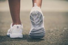 Espadrilles de la jeunesse sur des jambes de fille sur la route Photo stock
