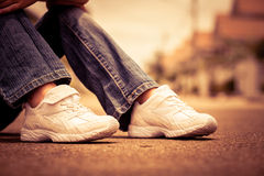 Espadrilles de la jeunesse sur des jambes de fille sur la route Photographie stock libre de droits