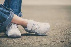 Espadrilles de la jeunesse sur des jambes de fille sur la route Images stock