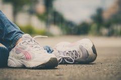 Espadrilles de la jeunesse sur des jambes de fille sur la route Photos libres de droits
