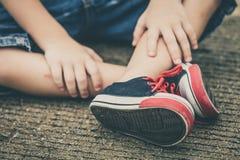 Espadrilles de la jeunesse sur des jambes de garçon sur la route Photographie stock