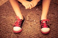 Espadrilles de la jeunesse sur des jambes de garçon sur la route Images stock