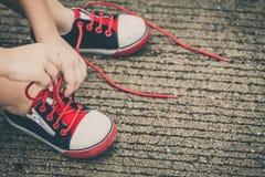 Espadrilles de la jeunesse sur des jambes de garçon sur la route Photo libre de droits