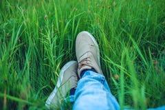 Espadrilles de la jeunesse sur des jambes des hommes dans des jeans sur l'herbe verte Image stock