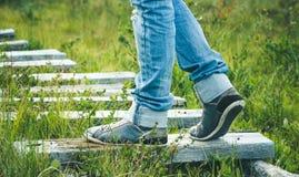 Espadrilles de pieds de femme marchant sur la route en bois extérieure Photos libres de droits