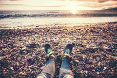 Espadrilles de pieds de femme sur le coucher du soleil de mer de plage Photos stock