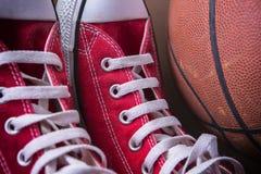 Espadrilles de sport et boule de panier Photos stock