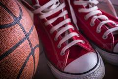 Espadrilles de sport et boule de panier Photographie stock