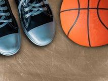 Espadrilles de sport et boule de panier Image libre de droits