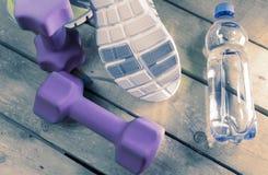 Espadrilles de sports et eau potable sur un fond en bois, modifiant la tonalité Photographie stock libre de droits