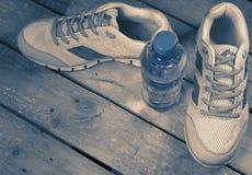 Espadrilles de sports et eau potable sur un fond en bois, modifiant la tonalité Photographie stock