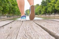 Espadrilles de toile sur des pieds sur le pont en bois Photos stock