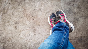 Espadrilles de vêtements pour hommes avec des jeans se tenant sur des jambes pour détendre après le voyage Images stock