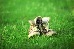 Espadrilles de vintage se reposant sur l'herbe Photo libre de droits