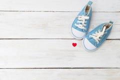 Espadrilles du ` s d'enfants pour un garçon de couleur bleue et d'un coeur rouge Moc Photographie stock