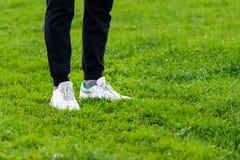 Espadrilles du ` s d'hommes sur leurs pieds dans l'herbe Images libres de droits