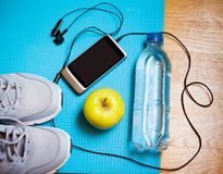 Espadrilles, eau, pomme, smartphone et écouteurs sur le tapis de yoga Photographie stock libre de droits