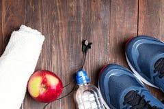 Espadrilles, eau, serviette et écouteurs sur la table en bois Photo libre de droits