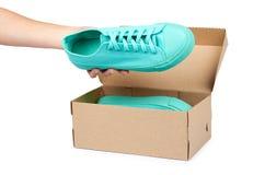 Espadrilles en caoutchouc de turquoise avec la main, chaussures occasionnelles d'isolement sur le fond blanc Photographie stock