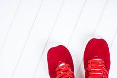 Espadrilles en cuir rouges sur un fond en bois blanc Images libres de droits