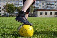 Espadrilles en lambeaux avec du ballon de football Photographie stock