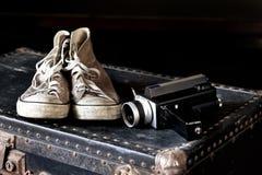 Espadrilles et appareil-photo de film sur la valise Photographie stock