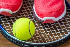 Espadrilles et balle de tennis sur une raquette Images libres de droits